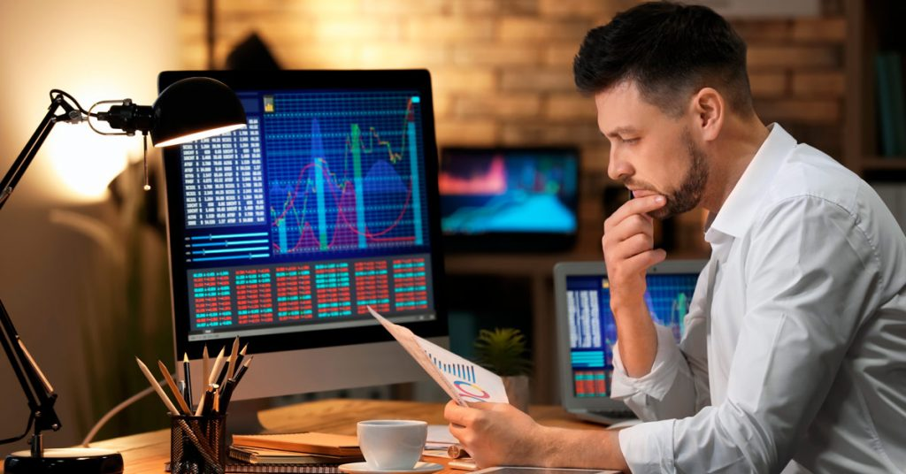 Man analyzing data with a computer monitor next to him displaying online trading charts